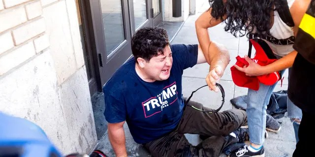 A supporter of President Donald Trump lies on the ground after he was attacked by counterprotesters in San Francisco, Saturday, Oct. 17, 2020. About a dozen pro-Trump demonstrators were met by several hundred counterprotesters as they tried to rally. (AP Photo/Noah Berger)