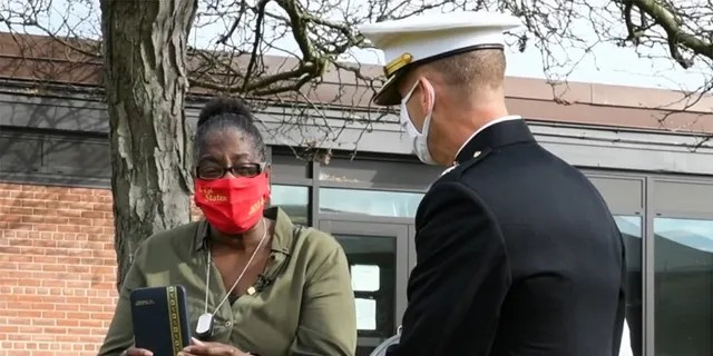 .A U.S. Marine Corps Major with 4th Combat Engineer Battalion presents Lance Cpl. Corey Staten's mother, Nancy Staten, the Navy and Marine Corps Medal during an award ceremony in Baltimore.