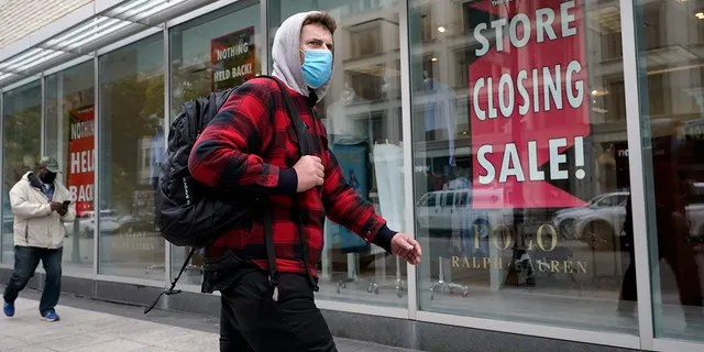 A passer-by walks past a store closing sign, right, in the window of a department store in Boston. Americans may feel whiplashed by a report Thursday, Oct. 29, on the economy's growth this summer, when an explosive rebound followed an epic collapse. The government estimate that the economy grew faster on an annualized basis last quarter than in any such period since record-keeping began in 1947. (AP Photo/Steven Senne)