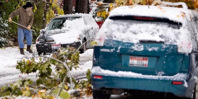 Tim Daulton clears snow off of his car across the street from a car with small tree branches on it on Saturday, Oct. 24, 2020, in Moscow, Idaho.
