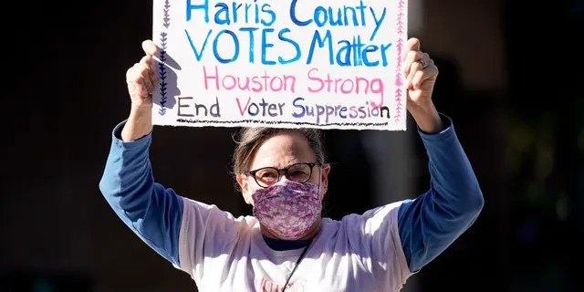 Demonstrator Gina Dusterhoft holds up a sign as she walks to join others standing across the street from the federal courthouse in Houston, Monday, Nov. 2, 2020, before a hearing in federal court involving drive-thru ballots cast in Harris County. (AP Photo/David J. Phillip)