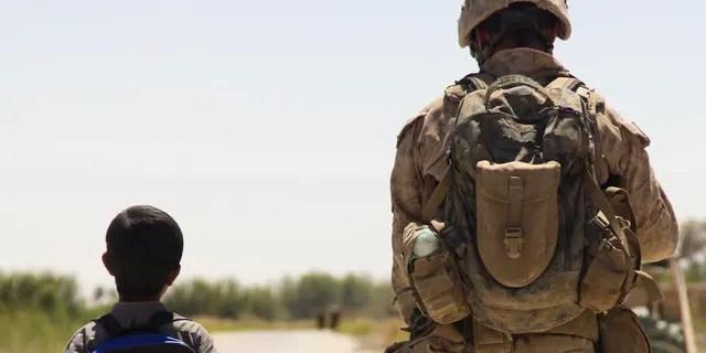 U.S. Marine patrols through the Nawa bazaar with an Afghan boy in Nawa District, Helmand Province (U.S Marine Corps photo by Lance Cpl. Jeremy Harris/Released)