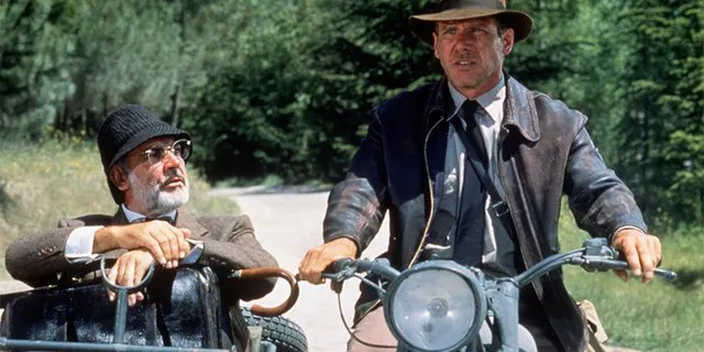 "American actor Harrison Ford as the eponymous archaeologist and Scottish actor Sean Connery as his father, Henry Jones, during the motorcycle chase scene from the film ""Indiana Jones and the Last Crusade"" in 1989"