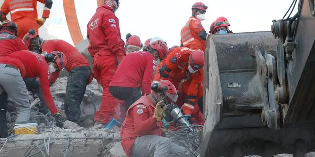 Members of rescue services search in the debris of a collapsed building for survivors in Izmir, Turkey, Sunday, Nov. 1, 2020.