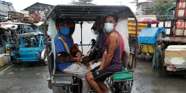 Residents wearing face masks to help prevent the spread of the coronavirus evacuate with their chickens to safer grounds as rains from a typhoon locally known as Goni start to pour in Manila, Philippines on Sunday Nov. 1, 2020. (Associated Press)