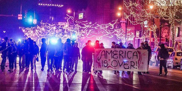 Police arrested protested who marched with fireworks to Uptown in Minneapolis, Tuesday, Nov. 3, 2020. They were cornered at Painter Park by the police. (Richard Tsong-Taatarii/Star Tribune via AP)