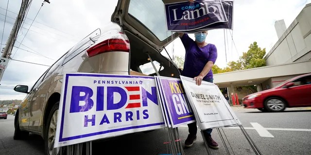 Anne Schirra Baker distributes campaign signs from her car outside the Butler County Democratic Committee headquarters in Butler, Pa., on Thursday, Oct. 15, 2020.