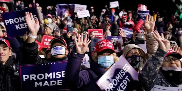 """Supporters hold up four fingers as they chant """"Four More Years"""" as they await President Trump for a campaign stop, Saturday, Oct. 31, 2020, at the Butler County Regional Airport in Butler, Pa."""
