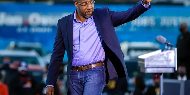 Democratic U.S. Senate candidate Rev. Raphael Warnock waves to supporters during a drive-in rally, Sunday, Jan. 3, 2021, in Savannah, Ga.