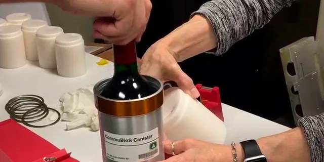 Researchers from Space Cargo Unlimited prepare bottles of French red wine to be flown from Wallops Island, Va., to the International Space Station on Nov. 2, 2019. (Space Cargo Unlimited via AP)
