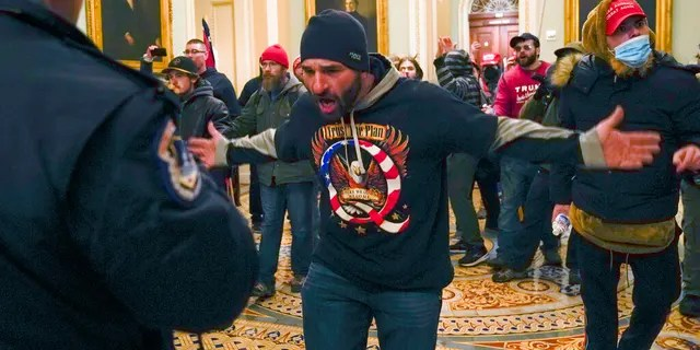 Trump supporters gesture to U.S. Capitol Police in the hallway outside of the Senate chamber at the Capitol in Washington.