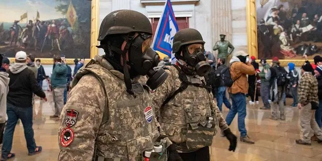 Supporters of President Trump wear gas masks and military-style apparel as they walk around inside the Rotunda after breaching the US Capitol in Washington, D.C., on Jan. 6, 2021.