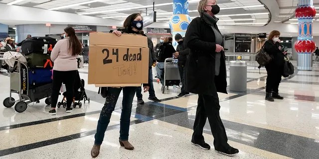 Mary Kay Hoffman, left, and Cindy Durham, right, wait for Sen. Ted Cruz to arrive, R-Texa, at the International Arrival Terminal at George Bush Intercontinental Airport on Thursday, February 18, 2021, in Houston.  (AP Photo / David J. Phillip)