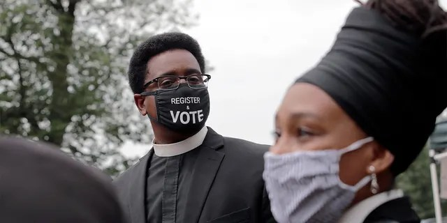 "FILE - In this Monday, July 20, 2020 file photo, the Rev. Rahsaan Hall, of the St. Paul AME Church in Cambridge, Mass., wears a mask which reads, ""Register & Vote"" outside the Statehouse in Boston. (AP Photo/Charles Krupa)"
