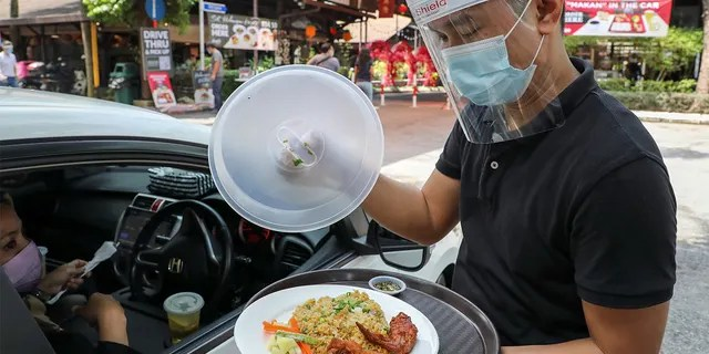 A waiter serves the customer outside the Padi House restaurant for a 'dine in car' service.  (Report / Lim Heuve Teng)