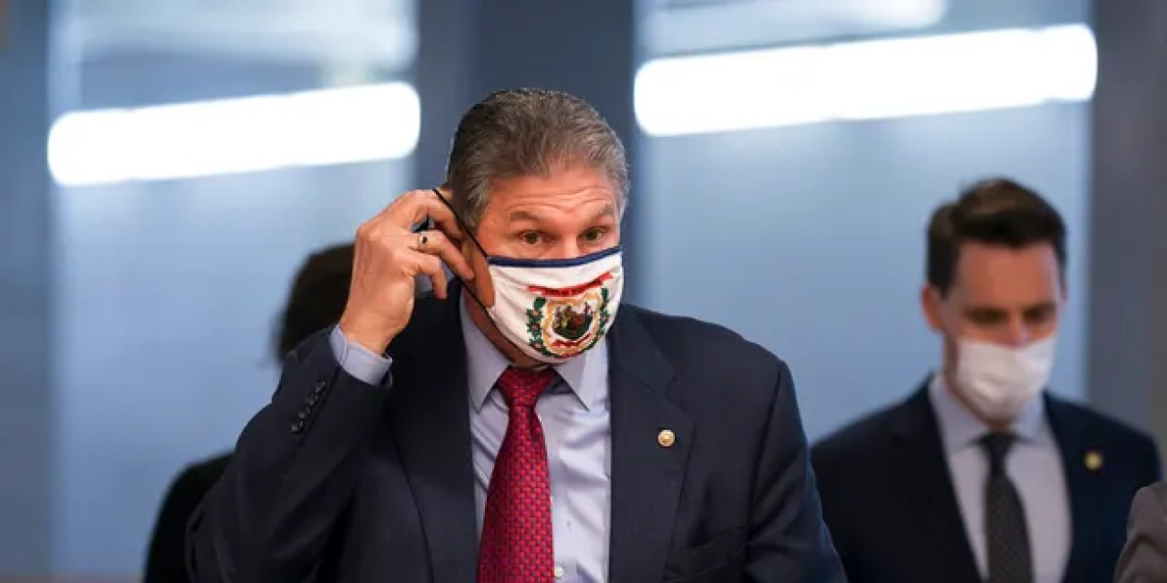 Sen. Joe Manchin, D-W.Va., adjusts his face mask as he arrives for votes on Biden administration nominees, at the Capitol in Washington, Tuesday, March 16, 2021. Manchin said he's against D.C. Statehood passing unilaterally through Congress. (AP Photo/J. Scott Applewhite)