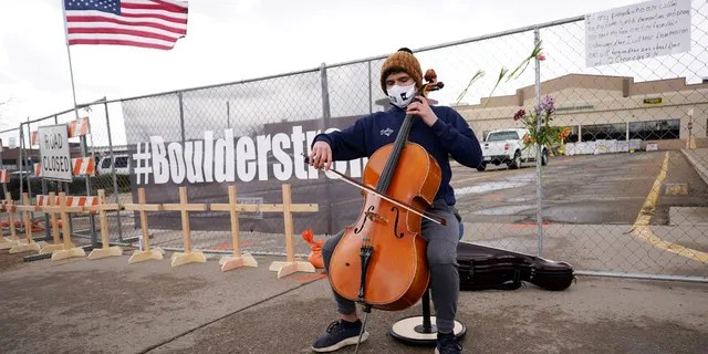 Louis Saxton plays his cello by a fence put up around the parking lot where a mass shooting took place in a King Soopers grocery store Tuesday, March 23, 2021, in Boulder, Colo. (AP Photo/David Zalubowski)