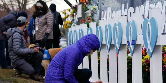 Adrienne Kroepsch of Golden, Colo., lights votive candles to place by crosses bearing the names of victims placed by the parking lot where a mass shooting took place in a King Soopers grocery store Tuesday, March 23, 2021, in Boulder, Colo. (AP Photo/David Zalubowski)
