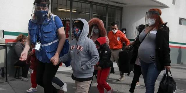 FILE - In this Friday, Feb. 26, 2021, file photo, a migrant family crosses the border into El Paso, Texas, in Ciudad Juarez, Mexico. (AP Photo/Christian Chavez, File)