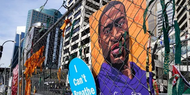 A picture of George Floyd hangs on a fence outside the Hennepin County Government Center, Tuesday, March 30, 2021, in Minneapolis where the trial for former Minneapolis police officer Derek Chauvin continues. (AP Photo/Jim Mone)
