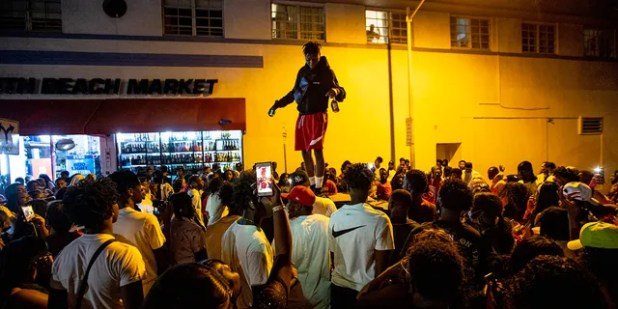A man stands in a car as the crowd defiantly gathers on the street as a speaker plays music an hour after curfew in Miami Beach, Florida, on Sunday, March 21, 2021. A curfew at 8 p.m. It spread in Miami Beach after police worked to contain unruly crowds of spring break tourists.  (Daniel A. Varela / Miami Herald via AP)