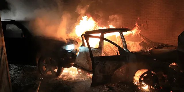 Hijacked cars burn at the peace wall on Lanark Way as rioting broke out in West Belfast, Northern Ireland, Wednesday, April 7, 2021. The police had to close roads into the nearby Protestant area as crowds from each divide attacked each other. (Associated Press)