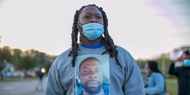 A demonstrator wears a shirt with an image of Andrew Brown Jr. on it during a march, Thursday, April 22, 2021, Elizabeth City, N.C., in reaction to the death of Brown, who was shot and killed by a Pasquotank County sheriff's deputy earlier in the week. (Robert Willett/The News & Observer via AP)