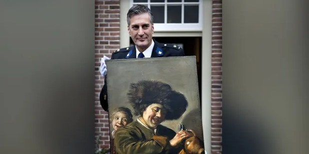 """This photograph taken on November 3, 2011 shows Alblasserwaard District Chief Bart Willemsen displaying the recovered painting. """"Two boys laughing"""" by Frans Hals that was stolen from the Leerdam Museum in May 2011 (Photo by ILVY NJIOKIKTJIEN / ANP / AFP via Getty Images)"""