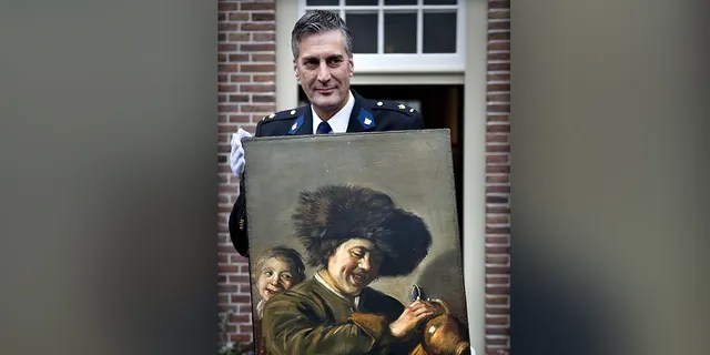 """This photograph taken on November 3, 2011, shows District Chief of Alblasserwaard, Bart Willemsen showing the recovered painting """"Two Laughing Boys"""" by Frans Hals which was stolen from the Leerdam Museum in May 2011. (Photo by ILVY NJIOKIKTJIEN/ANP/AFP via Getty Images)"""