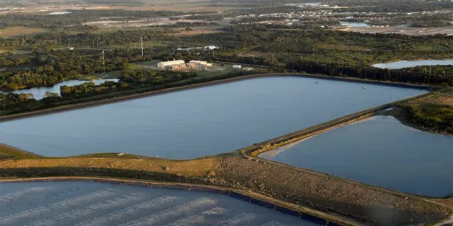 This photo shows a reservoir near the old Piney Point phosphate mine, Saturday, April 3, 2021 in Bradenton, Fla. Florida Gov. Ron DeSantis declared a state of emergency Saturday after a significant leak at a large pond of wastewater threatened to flood roads and burst a system that stores polluted waters. The pond where the leak was discovered is at the old Piney Point phosphate mine, sitting in a stack of phosphogypsum, a waste product from manufacturing fertilizer that is radioactive. (Tiffany Tompkins/The Bradenton Herald via AP)