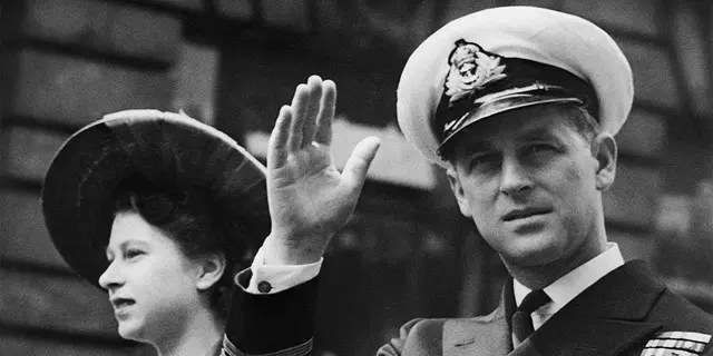 In this file photo from June 8, 1948, the Duke of Edinburgh seated next to Princess Elizabeth recognizes the cheering crowd as the open Landau crosses Fleet Street towards London's Guildhall.  Buckingham Palace officials say Prince Philip, the husband of Queen Elizabeth II, has died, it was announced on Friday April 9, 2021. He was 99 years old.  Philip spent a month in hospital earlier this year before being released on March 16 to return to Windsor Castle.  Philip, also known as the Duke of Edinburgh, married Elizabeth in 1947 and was the longest-serving husband in British history.