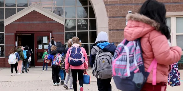 Students file into the Beebe School, in Malden, Mass., Monday, April 5, 2021, as they return to full-time in-person school.
