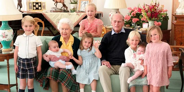In this undated handout photo provided by the Duke and Duchess of Cambridge, Britain's Queen Elizabeth and Prince Philip pose with their great-grandchildren. From left, Prince George, Prince Louis, Savannah Phillips (standing at rear), Princess Charlotte, Isla Phillips holding Lena Tindall, and Mia Tindall.