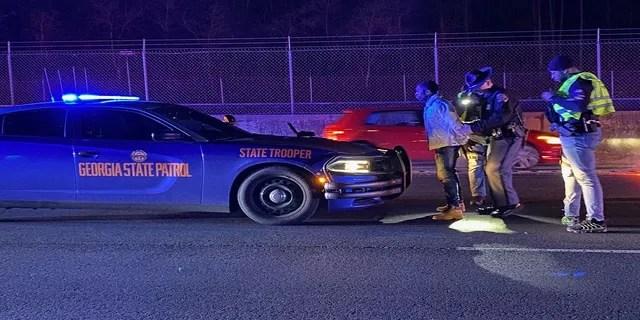 Smith, of Atlanta, is shown here being taken into custody. (Sandy Springs Police Department)