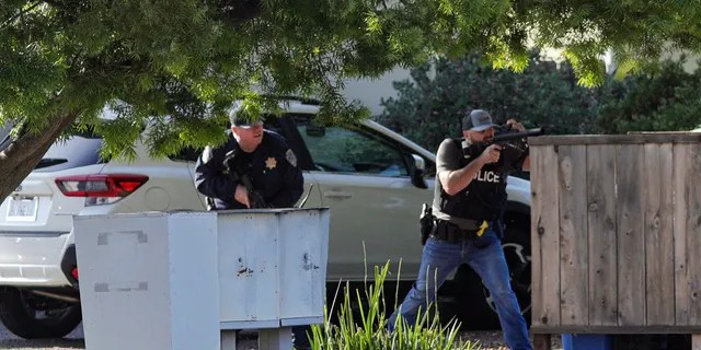 Officers take aim at an apartment across Camilla Court, Monday, May 10, 2021, in San Luis Obispo, Calif. Police said two police officers have been shot while serving a search warrant and the suspect has died. (David Middlecamp/The Tribune (of San Luis Obispo) via AP)
