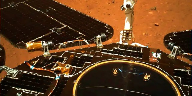 In this photo taken by China's Zhurong Mars rover and made available by the China National Space Administration (CNSA) on Wednesday, May 19, 2021, the rover's solar panels and antenna are deployed as the rover sits on its lander on the surface of Mars. (CNSA via AP)