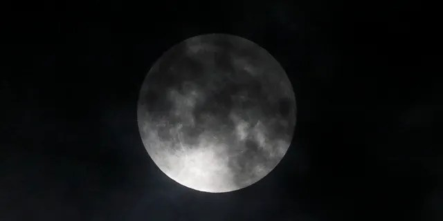 The lunar eclipse progress is seen behind the clouds over Santa Monica Beach in Santa Monica, Calif., Wednesday, May 26, 2021. The first total lunar eclipse in more than two years is coinciding with a supermoon for quite a cosmic show. (AP Photo/Ringo H.W. Chiu)