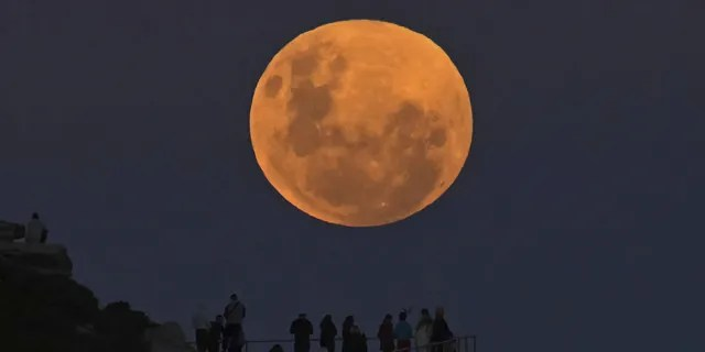 """SYDNEY, AUSTRALIA - MAY 26: People watch the """"Super Flower Blood Moon"""" rises over the Pacific Ocean at Bondi Beach in Sydney, Australia on May 26, 2021. The """"Super"""" moon observed in May is often defined as """"flower moon"""" as well, mainly due to association with flowers blooming at this time of year. During the eclipse, the moon turns into a deep blood-red color, known as """"blood moon."""" This celestial incident -- known as """"Super Flower Blood Moon"""" -- is the only full lunar eclipse of this year. (Photo by Steven Saphore/Anadolu Agency via Getty Images)"""
