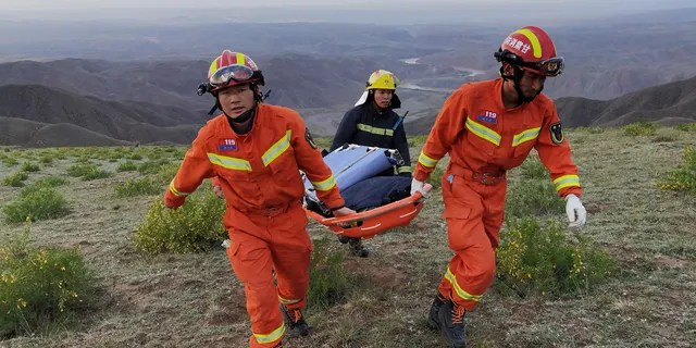 Rescuers carrying equipment as they search for runners who were competing in a 100-kilometre cross-country mountain race when extreme weather hit the area, leaving at least 20 dead, near the city of Baiyin in China's northwestern Gansu province.
