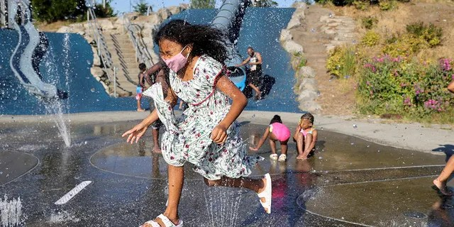 Isis Macadaeg, age 7, plays in a spray park at Jefferson Park during a heat wave in Seattle, Washington, U.S., on June 27, 2021. REUTERS/Karen Ducey