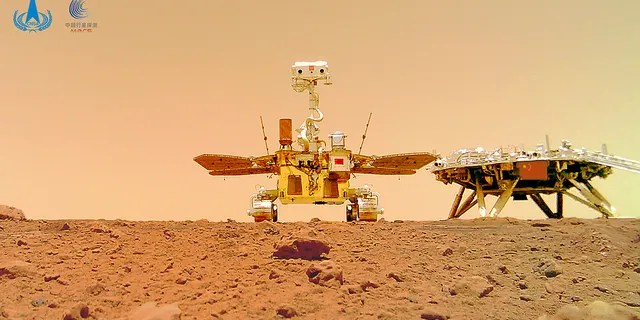 In this image released by the China National Space Administration (CNSA) on Friday, June 11, 2021, the Chinese Mars rover Zhurong is seen near its landing platform taken by a remote camera that was dropped into position by the rover. China on Friday released a series of photos taken by its Zhurong rover on the surface of Mars, including one of the rover itself taken by a remote camera. (CNSA via AP)