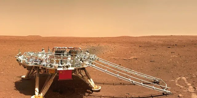 In this image released by the China National Space Administration (CNSA) on Friday, June 11, 2021, the landing platform with a Chinese national flag and outlines of the mascots for the 2022 Beijing Winter Olympics and Paralympics on Mars is seen from the rover Zhurong. China on Friday released a series of photos taken by its Zhurong rover on the surface of Mars, including one of the rover itself taken by a remote camera. (CNSA via AP)
