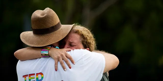 """Rep. Debbie Wasserman Schultz, D-Fla., is comforted after a truck drove into a crowd of people during The Stonewall Pride Parade and Street Festival in Wilton Manors, Fla., Saturday, June 19, 2021. Wilton Manors police tweeted Saturday night that the parade was canceled due to a """"tragic event."""" (Chris Day/South Florida Sun-Sentinel via AP)"""
