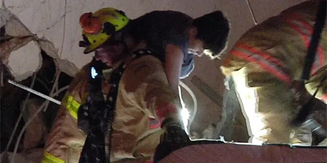 This photo taken from video provided by ReliableNewsMedia, firefighters rescue a survivor from the rubble of the Champlain Towers South Condo after the multistory building partially collapsed in Surfside, Fla., early Thursday. (ReliableNewsMedia via AP)