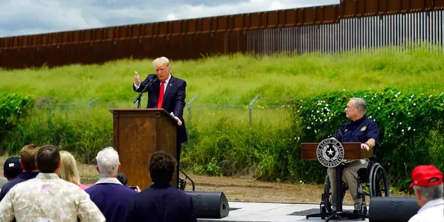 Texas Gov. Greg Abbott, right, listens to Former President Donald Trump, left, during a visit to an unfinished section of border wall, in Pharr, Texas, Wednesday, June 30, 2021. (AP Photo/Eric Gay)