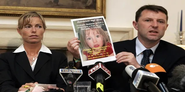 Kate McCann, left, looks on as her husband Gerry holds up a picture of their missing daughter Madeleine during a news conference in Rome, on May 30, 2007.
