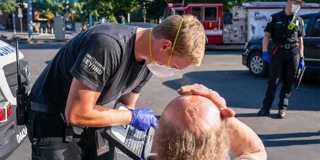 A paramedic with Falck Northwest ambulances treats a man experiencing heat exposure during a heat wave, Saturday, June 26, 2021, in Salem, Ore. (AP Photo/Nathan Howard)