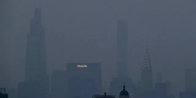 The Met Life and Chrysler buildings glow through a thick haze hanging over Manhattan, Tuesday, July 20, 2021, in New York.