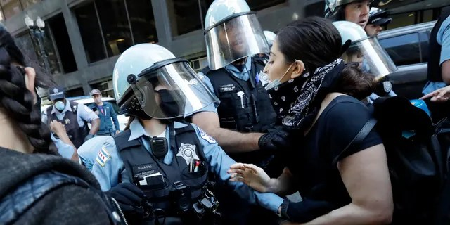 Chicago Police officers and protesters clash during a protest over the death of George Floyd in Chicago, Saturday, May 30, 2020. Floyd died after being taken into custody and restrained by Minneapolis police on Memorial Day in Minnesota. (AP Photo/Nam Y. Huh)