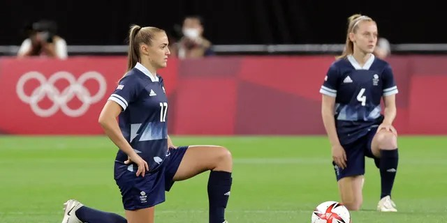 Britain's forward Georgia Stanway (L) and Britain's midfielder Keira Walsh take a knee before the Tokyo 2020 Olympic Games women's group E first round football match between Great Britain and Chile at the Sapporo Dome in Sapporo on July 21, 2021. (Photo by Asano Ikko/AFP via Getty Images)